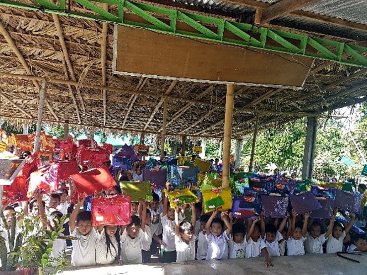 The Cabulihan Elementary kids waving their sets of school supplies from Sales Rain